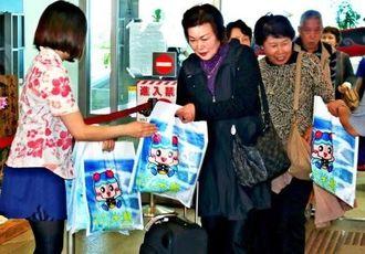 久米島空港に到着し、町観光協会職員らの歓迎を受けるFDAの乗客=1月29日(沖縄観光コンベンションビューロー提供)