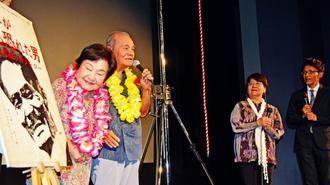 観覧1万人目となり、舞台であいさつする宮城伸夫さん(左から2人目)、泰子さん(左)夫妻。佐古忠彦監督(右)と内村千尋さんも聴き入った=17日、那覇市・桜坂劇場