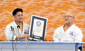 ギネス世界記録の公式認定証を手に、師匠の佐久本嗣男さん(右)と笑顔で記者会見する喜友名諒=2日、沖縄空手会館