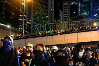 香港の政府本部庁舎に向けてレーザーを照射するデモ隊=18日(共同)