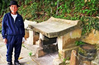 ウシジャーの神をまつる拝所を紹介する仲村渠善照さん。右側には大豆をつぶすときに使う臼もある=12日、那覇市古波蔵