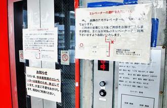 管理者の県が、故障や迂回(うかい)路を案内する紙を貼っている古島駅のエレベーター=12日、那覇市