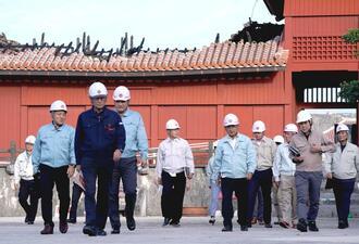 火災現場の視察を終えた県議会の土木環境委員会メンバー。後方は正殿入り口の奉神門=5日午後、那覇市首里(下地広也撮影)
