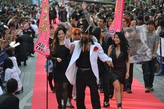 「やればできる」と何度も繰り返し言いながら、レッドカーペットを歩いたヒゲのかっちゃん(中央)=28日、沖縄市のゲート通り