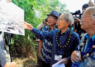 ホノウリウリ収容所跡地を訪れ、写真を見ながら当時の出来事を語る古堅実吉さん(中央)と渡口彦信さん(右)ら=ハワイ州オアフ島
