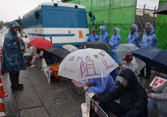 雨の中、米軍キャンプ・シュワブのゲート前で工事関係車両の進入に警戒する市民ら=10日午前7時15分ごろ、名護市辺野古