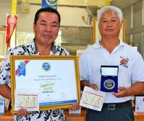 受賞メダルを披露する与那国水産加工の東郷代表(右)と小島達也営業担当=石垣市宮良、同社