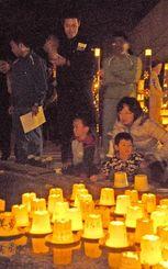 プラスチックの鉢にともした灯を水に浮かべて、鎮魂を祈る参加者ら=名護市・北部農林高校