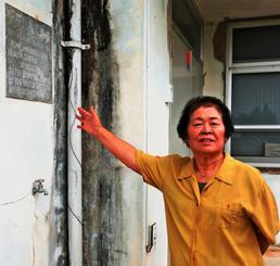 旧那覇保健所久米島支所の敷地内に立つ宮里恵美子さん。建物には1967年9月付で「アメリカ合衆国より琉球住民へ贈る」と刻まれたプレートが当時のまま残る=14日、久米島町