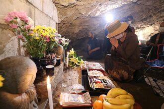 ガマの中に設けられた祭壇に手を合わせる遺族ら=3日午後1時10分ごろ、読谷村波平のチビチリガマ(代表撮影)