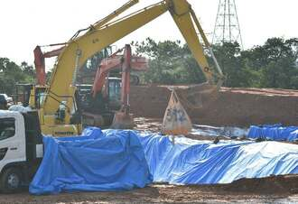 殺処分された豚が入った袋を、埋却地に下ろす重機=10日午前9時半ごろ、うるま市