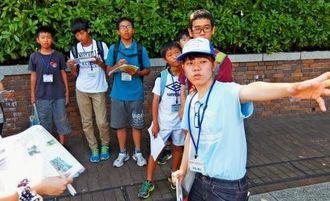 全国から参加した中学生らに原爆投下後の状況を伝える平良棟子さん(右)=8日午後、長崎市松山町の原爆落下中心地