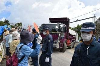東村高江のN1地区出入り口から出る工事車両に「森を壊すな」と抗議する市民ら=2日午前11時
