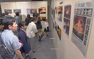 一足先に会場の展示を見る県新聞スクラップコンテスト受賞者ら=24日、那覇市久茂地・タイムスギャラリー