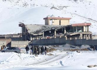 車での爆発攻撃を受けた後、崩れた軍施設の前に立つ人々=21日、アフガニスタン中部ワルダク州(ロイター=共同)
