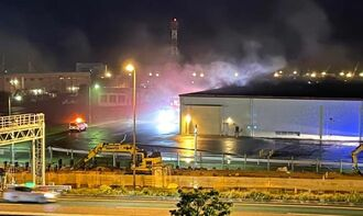 白煙が上がった米軍キャンプ・キンザー内にある倉庫=29日午後8時ごろ、浦添市仲西(読者提供)