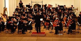 この日に合わせて作曲された交響曲を演奏する芸大の教員や学生ら=22日、那覇市・県立芸大奏楽堂ホール