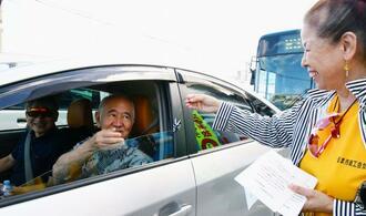 信号待ちのドライバーにお守りを配布する参加者=9月30日、うるま市・上平良川の交差点