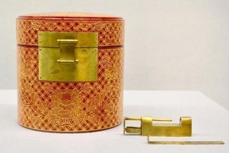朱漆塗りの「御印箱」と真ちゅう製の板バネ式の錠前=首里城公園・黄金御殿特別展示室