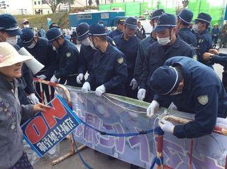 市民らが掲げた横断幕を取り外す機動隊員=19日午前10時、名護市辺野古