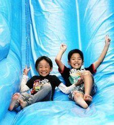 大型のエア遊具を元気よく滑り降りる子どもたち=沖縄市、東南植物楽園
