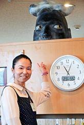 貸し出しカウンター奥の作品「Yの肖像」を指さす玉那覇千恵さん=21日、西原町立図書館