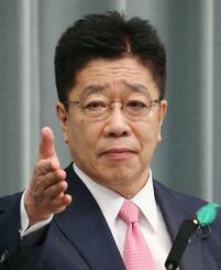 記者会見する加藤官房長官=19日午前、首相官邸