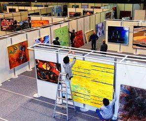 開幕を控え、入念に作品をチェックし展示作業が行われる沖展会場=18日午後、浦添市民体育館
