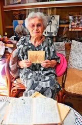 「一枚の写真」を手にする山川セツ子さん。手前は「シャッターを切る」と記された1944年10月13日付の日記=那覇市安里の自宅