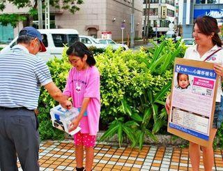 【募金活動】募金する人にお礼を述べながら受け取る親子連れ=2015年10月、那覇市・パレットくもじ前