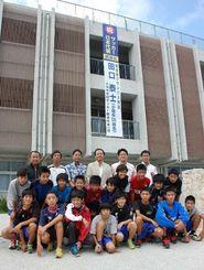 田口泰士選手を応援するために掲げられた懸垂幕とサッカー部部員ら=14日、小禄中学校
