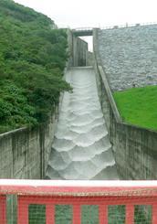 19日からの大雨で貯水量が100%を超え、オーバーフローする羽地ダム=20日、名護市