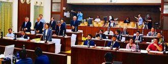 自衛隊「計画中止」を求める請願の採択に賛成し起立する野党議員と、不採択で着席する与党議員=18日、石垣市議会