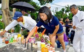 魂魄の塔に親戚同士で参拝に訪れ、線香を供える子ども=23日午前8時40分、糸満市米須