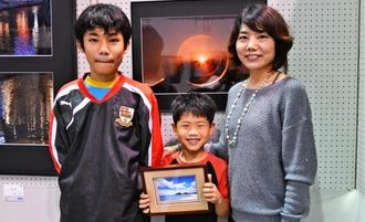 入場2万人目になった仲程大徒君(中央)と母、尚子さん(右)、兄の悠人君=3日、浦添市民体育館