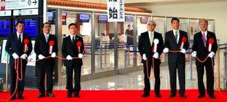 くす玉を割り国際線ターミナルビルの供用開始を祝う那覇空港ビルディングの花城順孝社長(右から3人目)ら