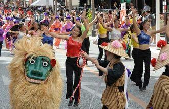 華やかなダンスと演奏を披露する西原高と南風原高の生徒たち=23日、那覇市・国際通り(古謝克公撮影)