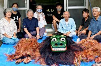 神獅子の虫干しとお披露目をする古謝集落の役員と獅子舞保存会役員ら=8月25日、沖縄市