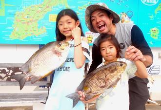 本部海岸で44センチ、1.9キロと40.5センチ、1.28キロのカーエーを釣った前當慎也さん(奥)=7月24日