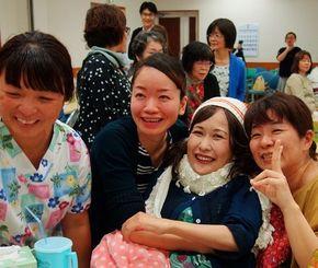 「感謝の会」参加者と一緒に写真に納まる當間光江さん(右から2人目)=4月29日、糸満市・南部病院