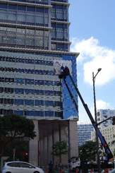 タイムスビルの壁面に貼られていく安室奈美恵さんの特大ポスター=9日午前10時17分、那覇市久茂地