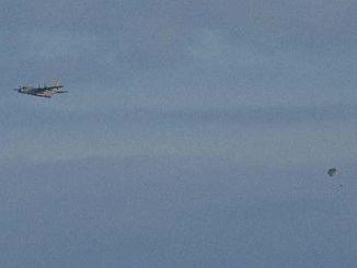 米軍嘉手納基地所属のMC130特殊作戦機から降下する兵士=25日午後6時43分、うるま市津堅島訓練場水域