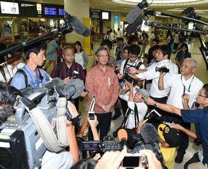 那覇空港に到着し国連人権理事会での演説について報告する翁長雄志知事(中央)=24日午後7時すぎ