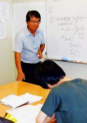 河上所長から数学の指導を受ける高校生=北谷町ニライセンター