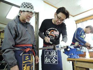 渡慶次理事長(左)から三線作りの指導を受けるひーぷーさん=20日、同組合店舗