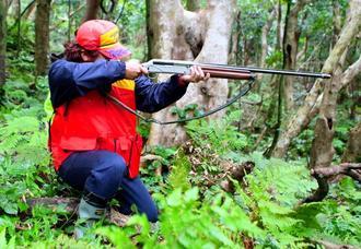 静寂の山中で、イノシシの出現に備えて猟銃を構える平良五月さん=石垣市内