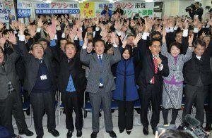 二期目の当選が確実となり、支持者と万歳三唱をする佐喜真淳氏(中央)=24日午後9時17分、宜野湾市野嵩の選挙事務所
