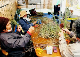 「ガンシナ注連七輪」を制作するため、草を選別する久高島のお年寄りたち=16日、南城市知念