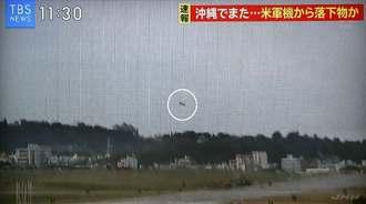 沖縄県宜野湾市の市立普天間第二小学校の運動場に、米軍ヘリから落下する窓のようなもの(円内)=13日(TBSテレビ/琉球放送の映像より)