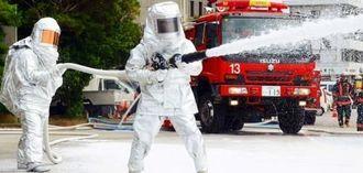 耐熱防護服を着て泡消火する消防隊員=12日、宜野湾市野嵩の市消防本部